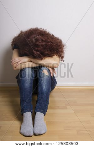 sad depressed young woman hiding her face sitting on floor