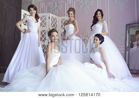 Beauty brides in bridal gowns indoors. Beautiful model girls in a white wedding dresses. Female portrait of cute ladies. Women with hairstyle poster