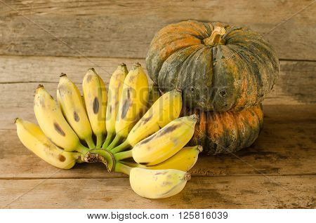 Still life with Bananas and pumpkins on wooden table