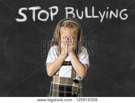 young sweet junior schoolgirl victim of bully crying sad standing in front of school class blackboard with chalk text stop bullying in school children bullied and education stress