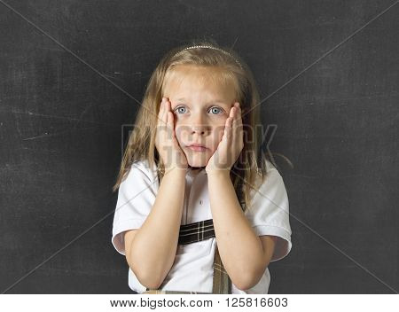 young sweet junior schoolgirl with blonde hair crying sad and shy standing isolated in front of school class blackboard wearing school uniform in children education stress and bullying victim