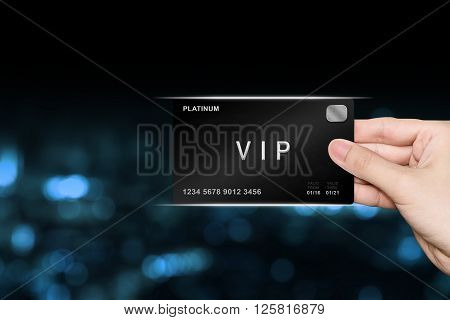 hand picking VIP or very important person platinum card on blur background