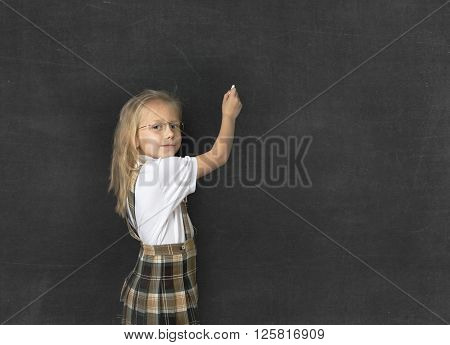 young sweet junior schoolgirl with blonde hair standing happy and smiling writing with chalk copy space in school classroom blackboard wearing school uniform in children education