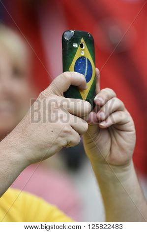 RIO DE JANEIRO BRAZIL - June 18 2014: secure mobile fan with cover of Brazil flag during the FIFA 2014 World Cup. Spain is facing Chile in the Group B at Maracana Stadium