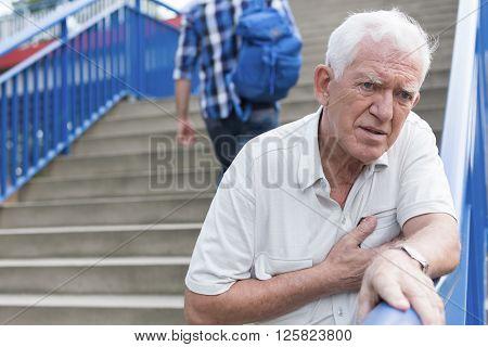 Senior weak man is walking down stairs