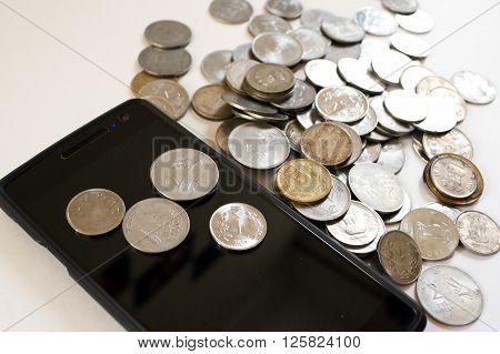 Mobile phone with indian currency set on a white background. Denoting payment through mobile and mobile wallets. Pile of old and new coins with phone poster