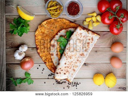 Lahmacun on a wooden table with ingredients. Turkish pizza