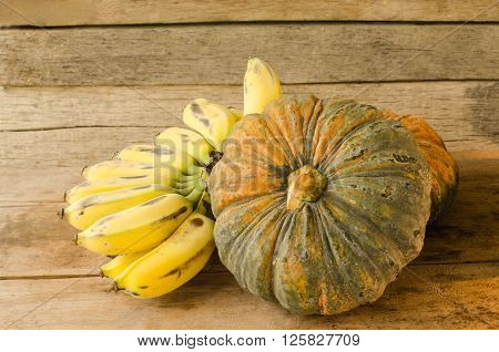 Still life with pumpkins and bananas on wooden table