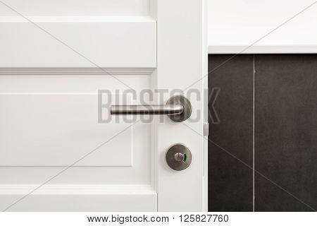 Open white door with metallic handle close up