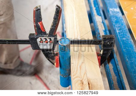 Frame wall construction. Closeup of clamp holding wooden beam