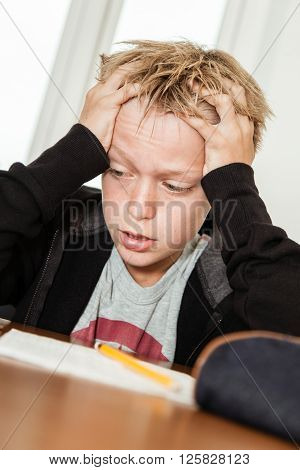 Single anxious blond boy in black sweater holding his head in frustration and desperation as he struggles to complete homework or study for a test poster