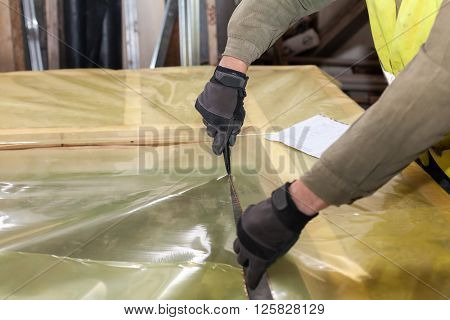 Building a wall for frame house. Worker cutting a protective film