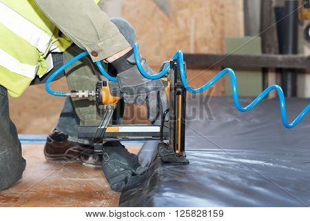 Building a wall for frame house. Worker use autofeed staple gun for attaching a vapor barrier