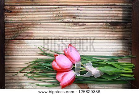 Pink tulip bouquet on dark wooden background