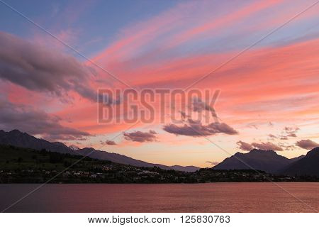In early morning of summer before sunrise with clouds sky becomes rosy and blue over Lake Wakatipu Queenstown New Zealand.