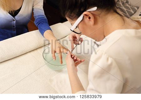 Manicurist cuts cuticles with nail client in the beauty salon. Shot from the back manicurist.