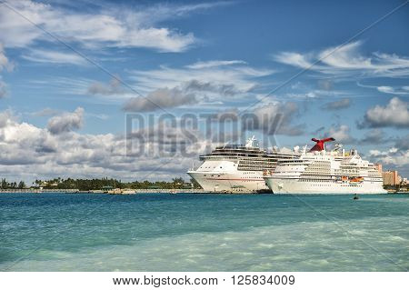 Nassau Bahamas - January 07 2016: Cruise ship Carnival Pride of Carnival Cruise Lines and luxury cruise ship Seven Seas Navigator of Regent Seven Seas Cruises standing in bay sunny day