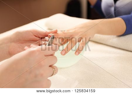 Close up of process of manicure at beauty salon. Manicurist clear cuticle professional scissors for manicure and pedicure.