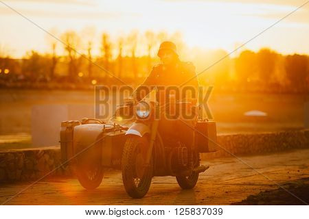 Unidentified re-enactor dressed as World War II german wehrmacht soldier rides on motorcycle in  rays of sunset sun.