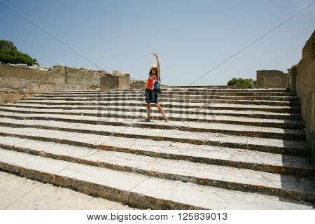 woman traveler tourist happy in landmark stairs of Festo or Festos palace ruins from XV century Before Christ Minoan greek city monument in Crete Greece Europe