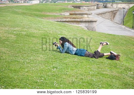 brunette adult tourist woman with blue jeans jacket and brown trousers lying on the green grass with camera travel photo as photographer taking picture of flower in Gijon park Asturias Spain