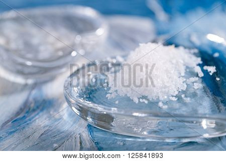 Fleur de sel sea salt sea salt with glass heart on blue abstract painted background
