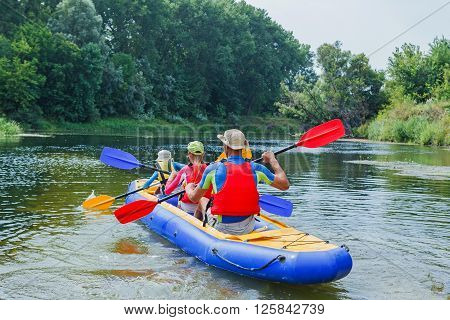 Back view of active happy family having fun together enjoying adventurous experience kayaking on the river on a sunny day during summer vacation