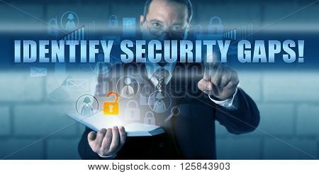 Manager touching IDENTIFY SECURITY GAPS! on a virtual touch screen interface. Business challenge metaphor and information technology concept for finding systems vulnerabilities and closing the gaps.