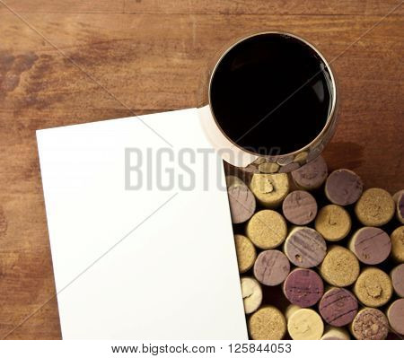 Glass of red wine shot from above on blurred wooden background with defocused wine corks from white and red wine with blank piece of white paper wine list or tasting invitation design template