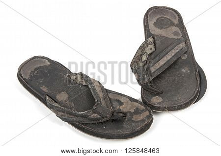 Isolated grubby pair of old worn-out black sandals on white