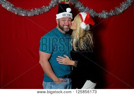 Cute couple in a holiday photo booth wearing santa hats and kissing.