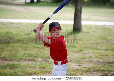 Portrait of Little baseball player holding a bat.