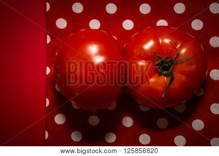 Two red tomatoes lying on the red tea-towel and red background