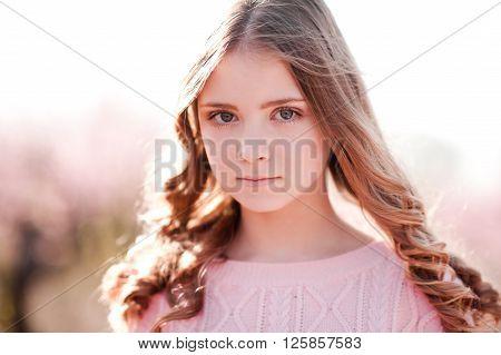 Beautiful blonde teen girl 14-16 year old posing outdoors. Looking at camera. Teenager hood.