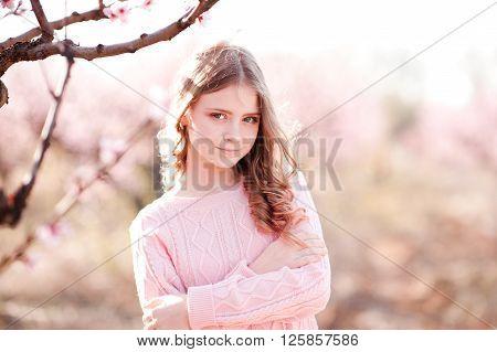 Beautiful blonde teenage girl 14-16 year old posing in peach garden. Looking at camera. Elegance.