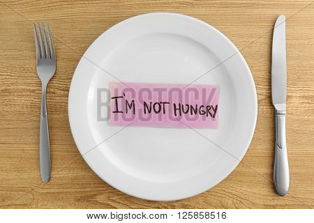 White plate with words I'm not hungry on wooden background