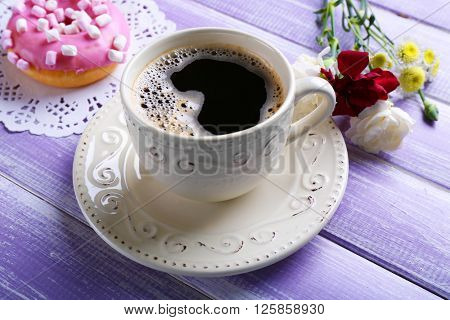 Cup of coffee with doughnut and flowers on wooden background