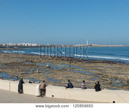 Casablanca Morocco - March 21 2014: The tourist relax themselves on the beach near Grand Mosque of Hassan II on March 21 2014 in Casablanca Morocco