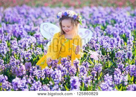Beautiful girl playing in blooming hyacinth flower field. Kids princess birthday party with fairy costume butterfly wings and magic wand. Children play in spring flowers. Child picking hyacinths.