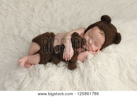 Three week old newborn baby boy wearing a brown crocheted bear hat and shorts. He is sleeping on a white flokati rug and holding a matching stuffed bear toy.