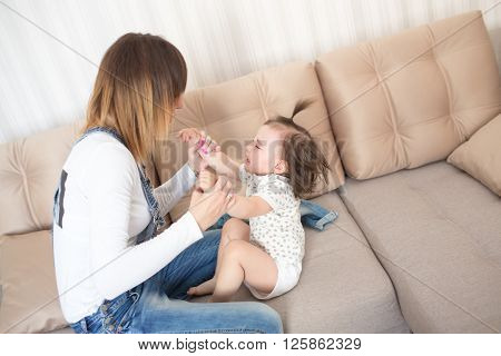 Woman soothes crying daughter. Focus on child