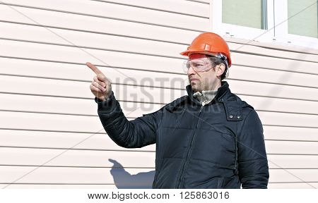 Worker on a construction site in winter gives instructions gestures ** Note: Visible grain at 100%, best at smaller sizes