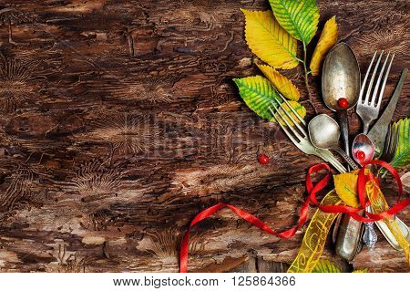 Vintage silverware on rustic wooden background with autumn decoration Organic Food concept. Vintage cutlery, antique silverware, fork, knife and a rose flower with rough cloth on an old wooden background, wooden background, Restaurant menu background,