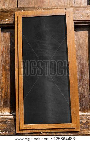 Empty blackboard with wooden frame hanging on a rustic wooden door