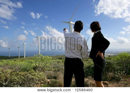 Young man and young woman in suit face to a wind turbine