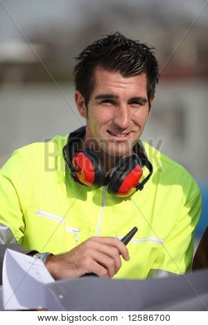 Portrait of a young worker with walkie-talkie and noise-canceling headphones