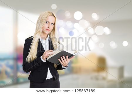 Pretty businesswoman with journal in blurry interor