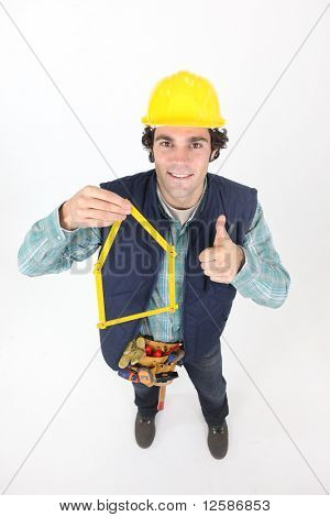 Portrait of a young worker with a double folding ruler on white background