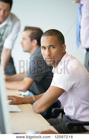 Portrait of a young man in front of a computer