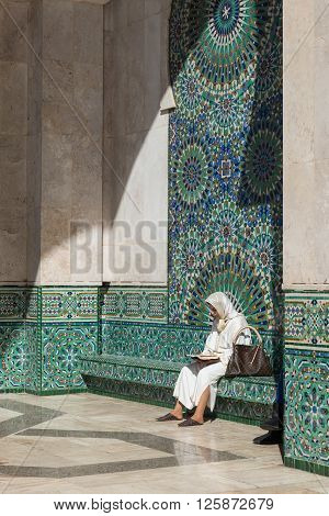 Casablanca Morocco - March 21 2014: One muslim woman sits in front of the colourful mosaic and reads book in Grand Mosque of Hassan II on March 21 2014 in Casablanca Morocco